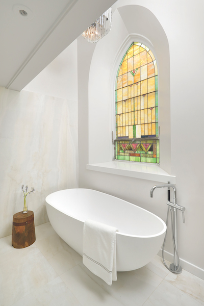 White bath tub and stained glass window