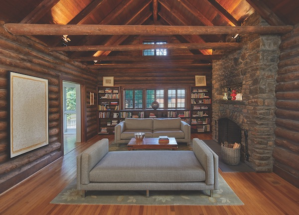 Living room with sofa and fireplace in log cabin open frame