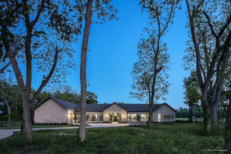 Twilight view of Texas custom home stone exterior with breezeway in the middle