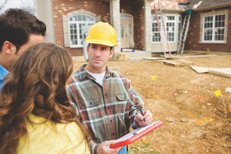 Couple with construction manager wearing a hard hat